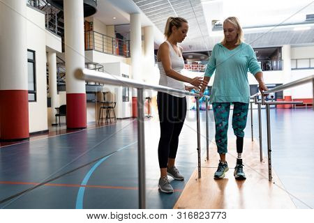 Front view of female physiotherapist helping disabled senior woman walk with parallel bars in sports center. Sports Rehab Centre with physiotherapists and patients working together towards healing