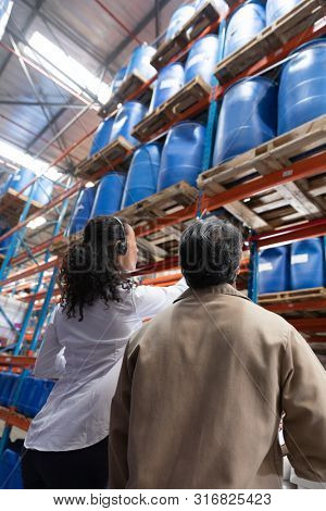 Low angle view of female manager and male staff interacting with each other while checking stocks in warehouse. This is a freight transportation and distribution warehouse. Industrial and industrial