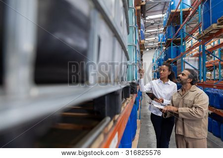 Female manger and male staff interacting with each other while checking stocks in warehouse. This is a freight transportation and distribution warehouse. Industrial and industrial workers concept