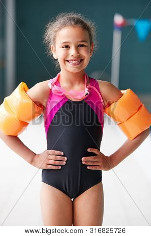 Portrait Of Girl Wearing Armbands Standing By Edge Of Swimming Pool Ready For Lesson
