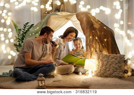 family, hygge and people concept - happy mother, father and little daughter reading book with torch light in kids tent at night at home