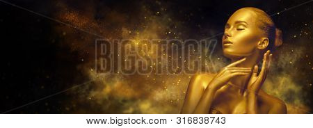 Gold Christmas Woman. Beauty fashion model girl with Golden make up, hair and jewellery, on black background with magic dust. Ads. Gold glowing skin. Metallic, glance Fashion art portrait, make up