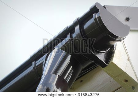 Rain Gutter Pipeline System Installation. Roofing Construction. Rain Gutter System And Roof Protecti