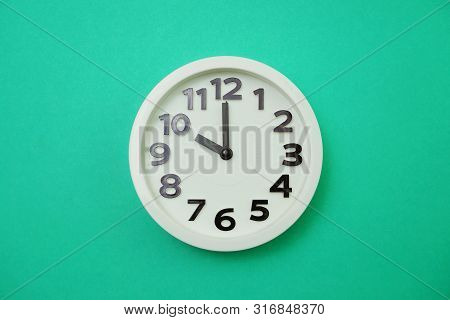 White Round Clock Showing Ten O'clock On Green Background