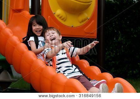 Happy Asian Girl And Caucasian Boy Playing Slide At School, Pre School Kids At Playground With Happi