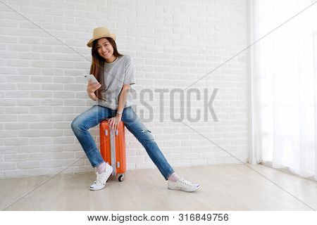 Young Asian Woman Sitting On Luggage Holding Smartphone In White Room Background, Happy Teenage Girl