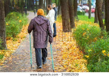 Senior Woman Enjoying Nordic Walking At Beautiful Colorful Autumn Park. Old Age Person Doing Pole Wa