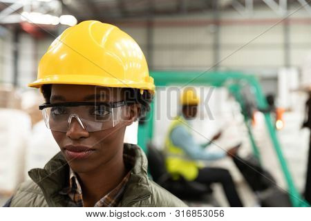 Close-up of female worker looking at camera in warehouse. This is a freight transportation and distribution warehouse. Industrial and industrial workers concept