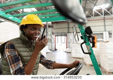 Happy female worker talking on walkie-talkie while driving forklift in warehouse. This is a freight transportation and distribution warehouse. Industrial and industrial workers concept