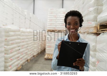 Portrait of female manager with headset writing on clipboard in warehouse. This is a freight transportation and distribution warehouse. Industrial and industrial workers concept