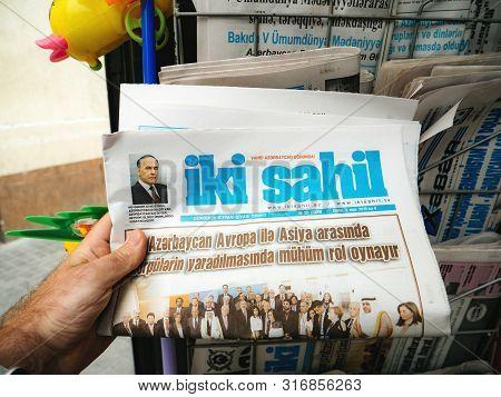 Baku, Azerbaijan - May 3, 2019: Man Hand Buy Shop For Fresh Newspaper Iki Sahil At The Press Kiosk I