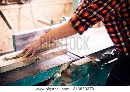 Young handsome joiner working with wood in his carpentry workshop poster