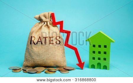 Money Bag With The Word Rates, Down Arrow And Wooden House. The Concept Of Reducing Interest Rates O