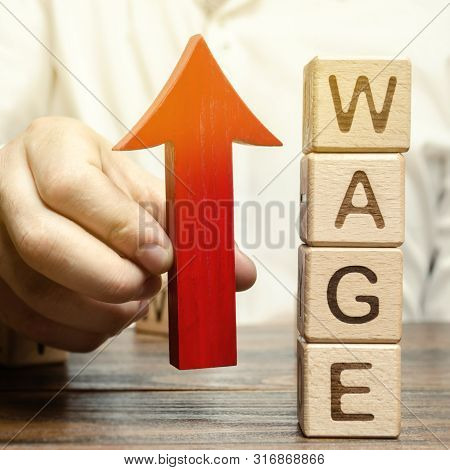 Businessman's Hand Holds Red Arrow Up Near Wooden Blocks With Word Wage. Salary Increase Concept. Wa