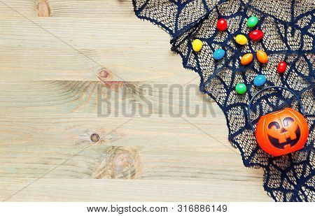 Halloween background. Spider web, cobweb lace and smiling jack decorations - Halloween tiny bag and candies - as the symbols of Halloween on the wooden background. Halloween card