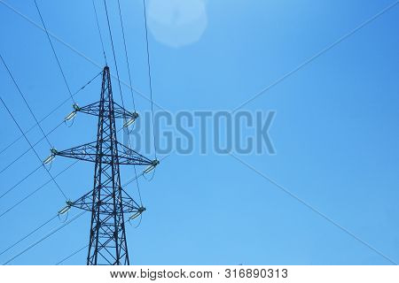 High Voltage Electrical Pole. Electricity Pole Against Blue Sky. Transmission Line Of Electricity. C