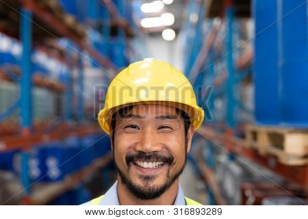 Close-up of happy Asian male worker looking at camera in warehouse. This is a freight transportation and distribution warehouse. Industrial and industrial workers concept