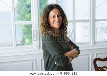 Beautiful middle age woman at home smiling cheerful with arms crossed