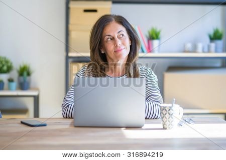 Middle age senior woman sitting at the table at home working using computer laptop smiling looking to the side and staring away thinking.