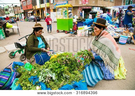 Puno, Bolivia - Jan 5, 2019: Unindentified woman in traditional costume sale a vegetable on the street of Puno city town on the Lake Titicaca, Bolivia.