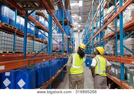 Rear view of female worker showing something to male worker in warehouse. This is a freight transportation and distribution warehouse. Industrial and industrial workers concept