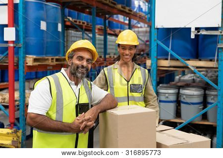 Happy male and female worker looking at camera in warehouse. This is a freight transportation and distribution warehouse. Industrial and industrial workers concept