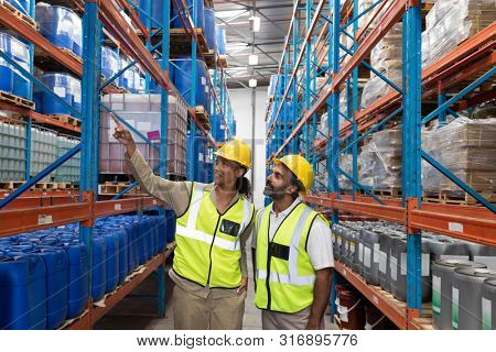 Front view of female worker showing something to male worker in warehouse. This is a freight transportation and distribution warehouse. Industrial and industrial workers concept