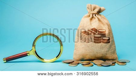 Money Bag And Magnifying Glass. Find A Money. The Concept Of Finding Sources Of Investment And Spons