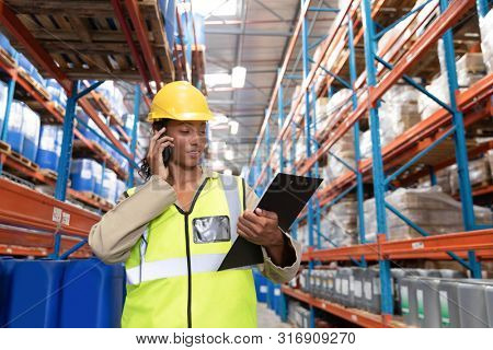 Front view of female worker looking at clipboard while talking on mobile phone in warehouse. This is a freight transportation and distribution warehouse. Industrial and industrial workers concept