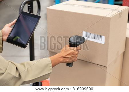 Close-up of female worker scanning package with barcode scanner while using digital tablet in warehouse. This is a freight transportation and distribution warehouse. Industrial and industrial workers