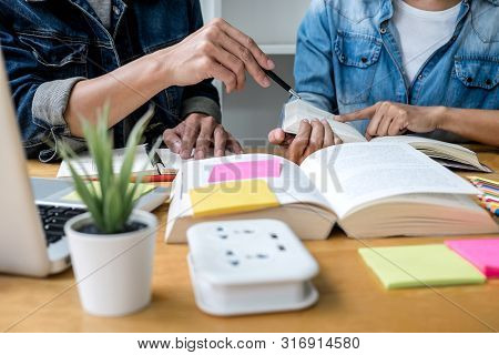 High School Tutor Or College Student Group Sitting At Desk In Library Studying And Reading, Doing Ho