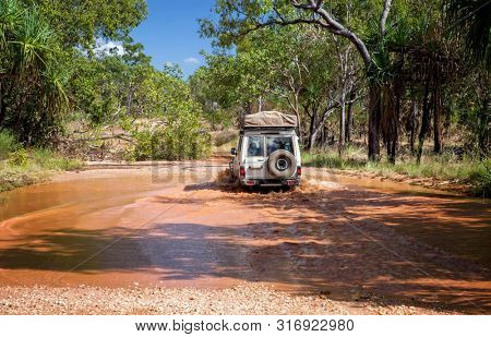 Western Australia – Flooded Outback gravel road with 4WD car crossing the waterhole at the savanna