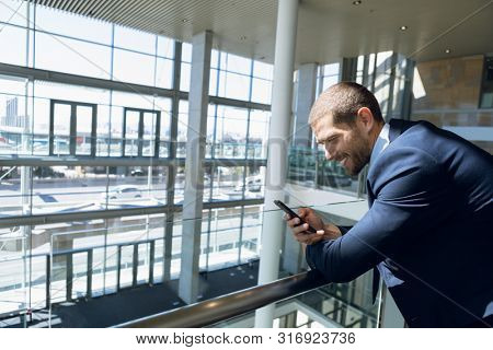 Side view of young Caucasian businessman looking down smiling at his smartphone. He is standing leaning on a handrail in the glass walled atrium of a modern business lobby. Modern corporate start up
