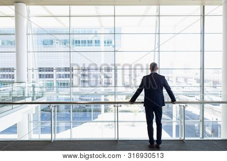 Full length back view of young Caucasian businessman standing in an empty glass walled office looking out of office window. Modern corporate start up new business concept with entrepreneur working