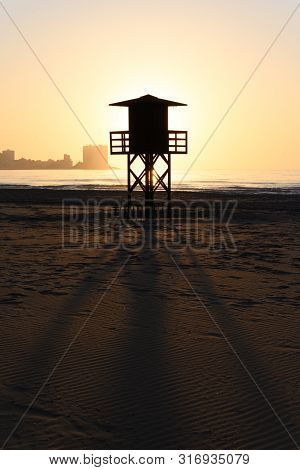 Stock Picture Of A Lifeguard Watchtower In Silhouette, At Cullera Beach In Spain.