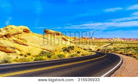Sunrise Over The Colorful Aztec Sandstone Rock Formations Along The White Domes Road As It Winds Thr