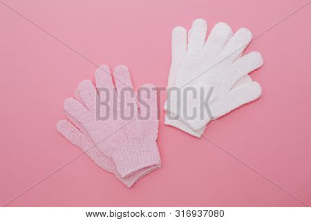 Woman exfoliating massage glove for shower on pink background.Gloves for use in the shower for massage and scrub. Beauty background with cosmetic products. Beauty, health and spa concept poster