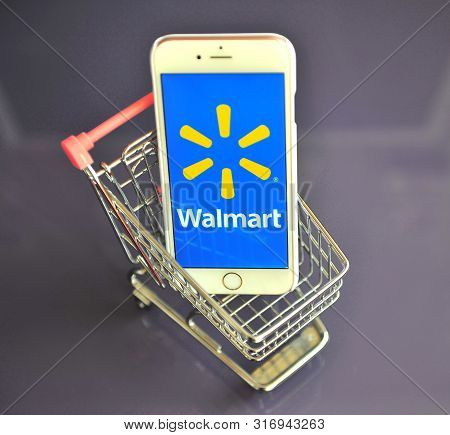 Iphone With Walmart Logo In Mini Shopping Cart On Table
