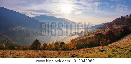 View From A Mountain Top In To The Foggy Valley. Beautiful Autumn Landscape. Forested Hills In Fall