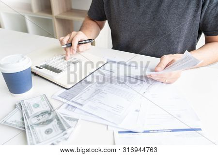Man Using Calculator And Calculate Bills Receipt In Home Expenses Payments Costs With Paper Note, Fi