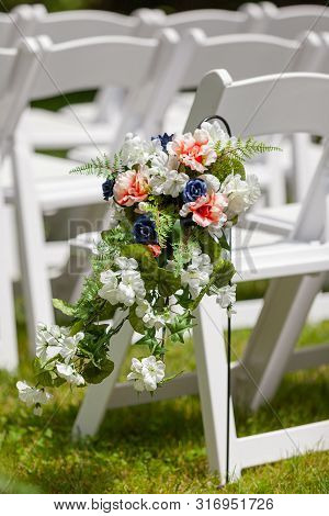 Outdoor Wedding Ceremony Artificial Flowers By White Chairs