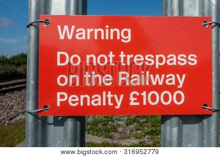 Do Not Trespass On The Railway Warning Sign On A Palisade Fence