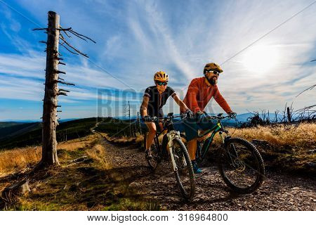 Cycling woman and men riding on bikes at sunset mountains forest landscape. Couple cycling MTB enduro flow trail track. Outdoor sport activity.