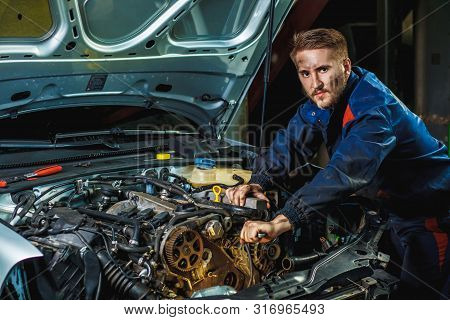 Close Up Hands Of Unrecognizable Mechanic Doing Car Service And Maintenance. Mechanic Working In Car