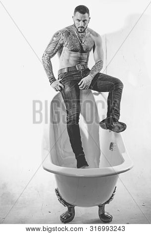 Hispanic man with muscular torso sitting on bath edge. Brutal latino man relaxing in bath. Spa bath and jacuzzi. Black and white photo poster
