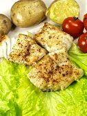 Fried white fish on a plate with potatoes salad lime and tomatoes poster