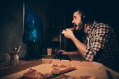 Close up side profile view photo he him his guy videogame headset microphone teammates concentrated look screen hand arm put pizza slice mouth wear casual plaid checkered shirt cafe table indoors poster