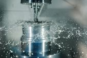 CNC milling machine sharpens the detail, splashing coolant fly around poster