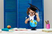 Clever and smart child, prodigy. A little girl in a graduation cap is examines a schoolbook through the glasses. Sitting at a desk with books on blue wooden wall background poster