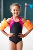 Portrait Of Girl Wearing Armbands Standing By Edge Of Swimming Pool Ready For Lesson poster